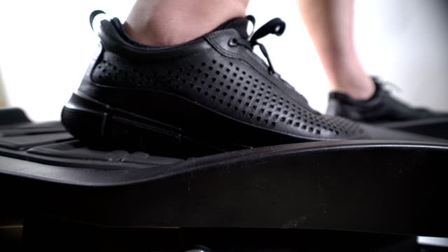 Male-feet-in-sneakers-on-foot-pedals-of-cross-trainer-during-workout