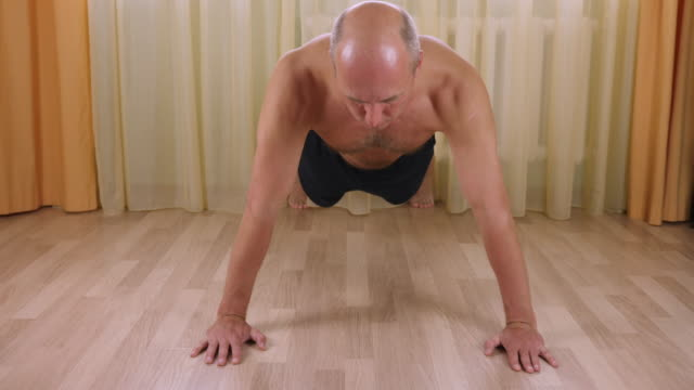 Adult-caucasian-man-pushing-up-from-floor-at-home-living-room-Workout-training-Front-view-close-up