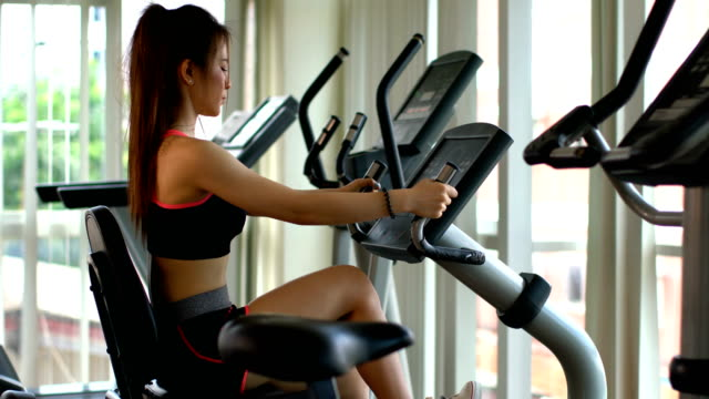 Sport-woman-work-out-with-exercising-bike-in-gym
