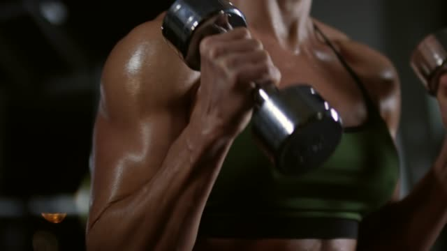 Muscular-Woman-in-Sports-Bra-Training-with-Dumbbells