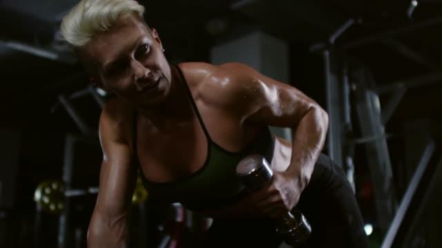Muscular-Female-Bodybuilder-Doing-Bent-Over-Dumbbell-Curls
