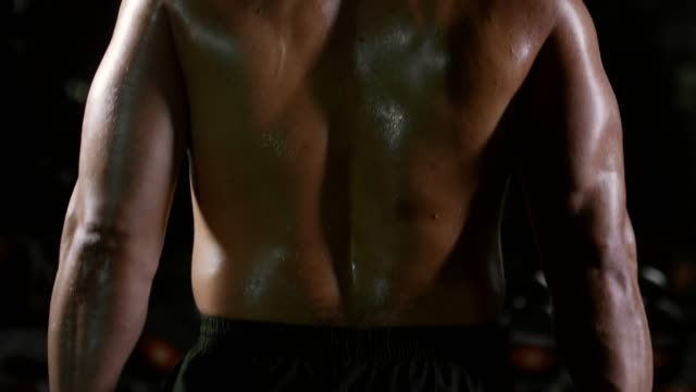 Rear-View-of-Muscular-Man-Exercising-with-Dumbbell