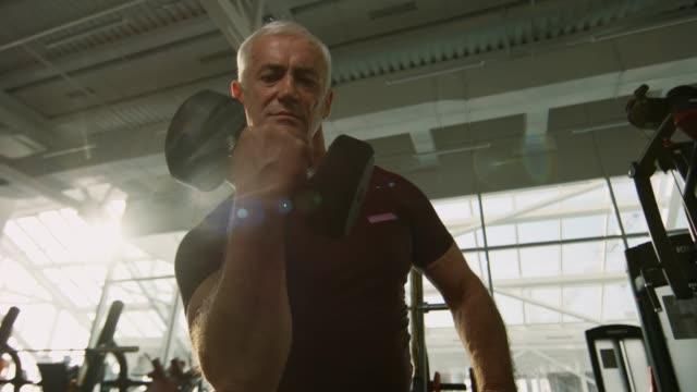 Sporty-Elderly-Man-Training-with-Dumbbell