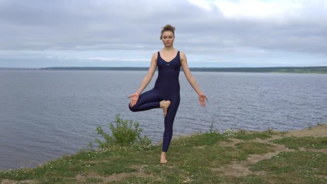 Yoga-woman-in-sportswear-pose-against-lake