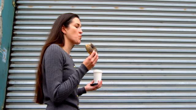 Hermosa-mujer-que-donuts-mientras-camina-en-la-ciudad-de