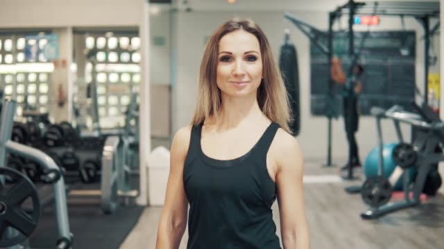 Slowmotion-shot-of-Young-fit-woman-walking-through-gym-
