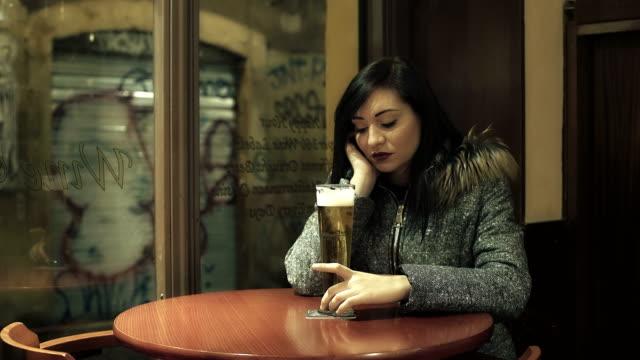mujer-deprimida-en-el-pub-refleja-en-frente-de-una-pinta-de-cerveza