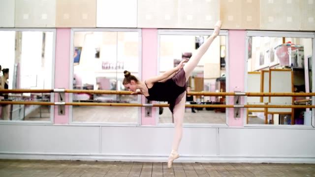 im-Tanzsaal,-führt-jungen-Ballerina-in-lila-Anzug-elegant-eine-bestimmte-Ballett-Übung-Arabeske-in-Neigung,-stehen-in-der-Nähe-von-Barre-am-Spiegel-in-Ballett-Klasse