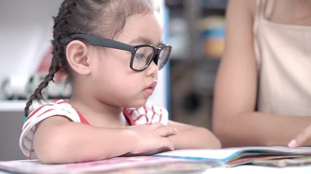 Ein-kleines-Mädchen-das-mit-ihrer-Mutter-sitzt-und-liest-
