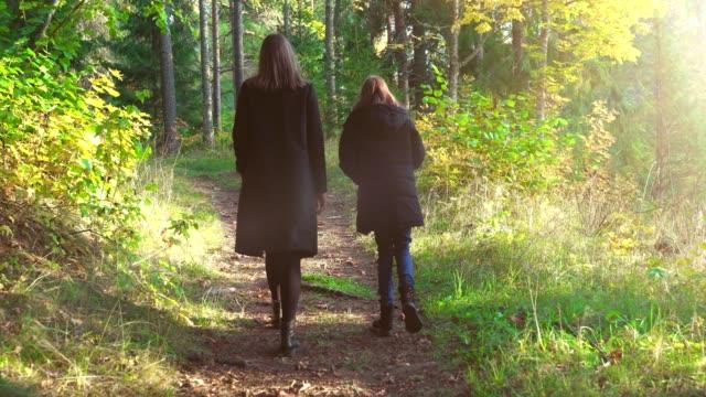 Frau-und-ihre-Tochter-gehen-im-Herbstwald-