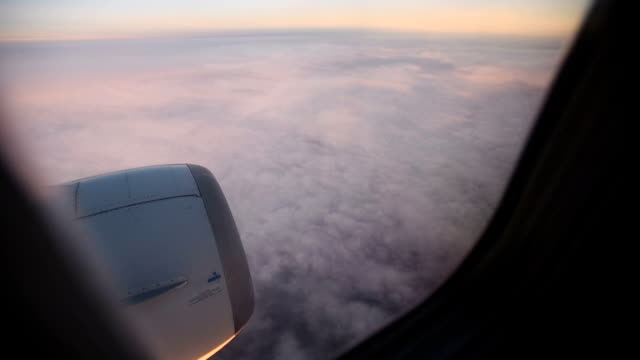 Purple-clouds-seen-through-the-window-of-jet-airplane-at-the-sunset-HD-video-High-Definition