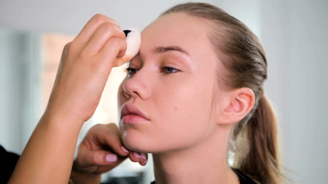 Unrecognizable-visagist-applying-fluid-foundation-on-young-woman-s-face-using-sponge-Professional-makeup-in-salon-Nude-makeup