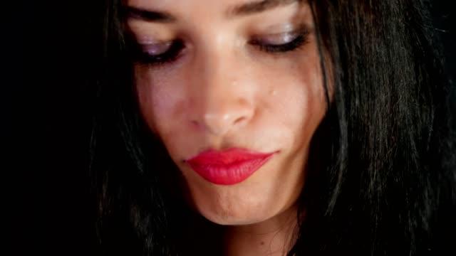 Retrato-de-una-atractiva-mujer-morena-con-rojo-labios-que-danza-y-juguetonamente-intenta-en-elegantes-copas,-espectáculos-y-sexualmente-mirando-a-cámara-en-estudio.-fondo-gris-oscuro
