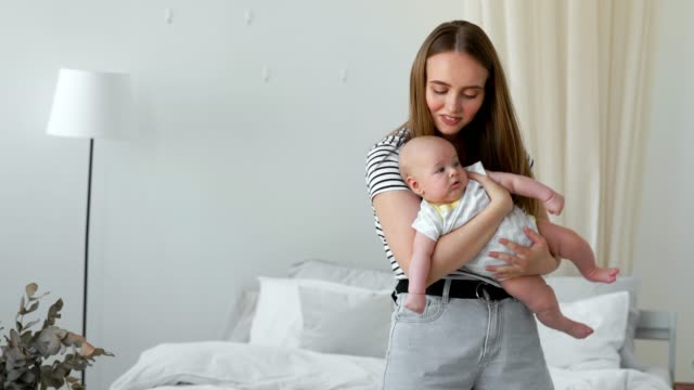 The-concept-of-a-modern-young-family-in-a-white-apartment-Mom-puts-the-baby-to-bed-singing-him-a-lullaby