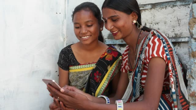 Two-Indian-girls-in-a-village-house-in-rural-Indian-share-laugh-on-mobile-phone-forward-video-joke-emoji-photo-on-their-touch-screen-funny-hilarious-busy-occupied-laughter-company-teamwork-bonding