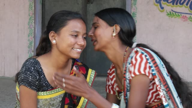 Two-girlfriends-share-whisper-news-laugh-smile-gossip-tell-secrets-stories-rumor-look-around-two-shot-static-close-up-rural-Indian-traditional-costume-dress-makeup-pretty-beautiful-home-love-share