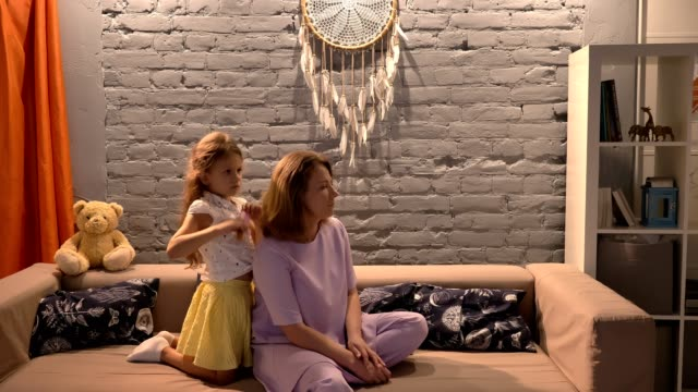 Little-daughter-brushing-her-mother-hair-with-hairbrush-sitting-on-sofa-in-modern-living-room-family-concept-indoors