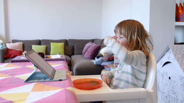 little-child-eating-and-watching-tablet