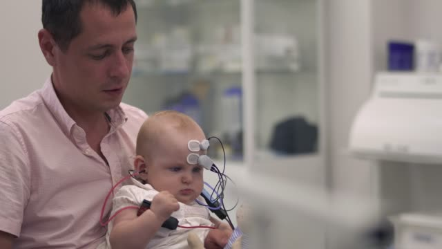 Dad-is-holding-a-baby-with-medical-sensors-on-hands