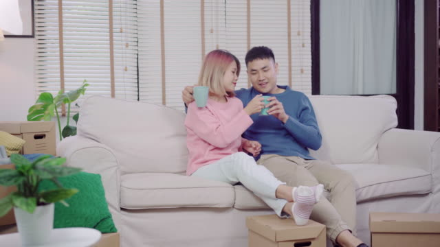 Attractive-Asian-sweet-couple-enjoy-love-moment-drinking-warm-cup-of-coffee-or-tea-in-their-hands-on-sofa-in-the-living-room-at-home-Husband-and-his-wife-relaxing-at-home-concept-