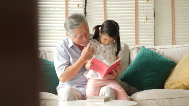 Asian-senior-grandfather-with-a-small-granddaughter-reading-book-together-at-home-Senior-lifestyle-family-concept-