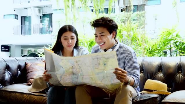 Touristen-paar-auf-der-Suche-auf-der-Landkarte-in-der-Lobby-