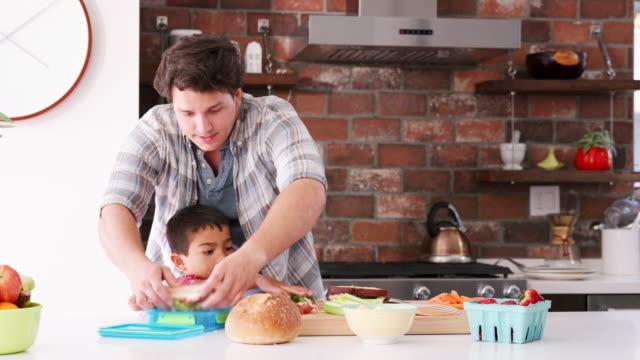 Padre-e-hijo-haciendo-sándwiches-para-el-almuerzo-en-la-cocina
