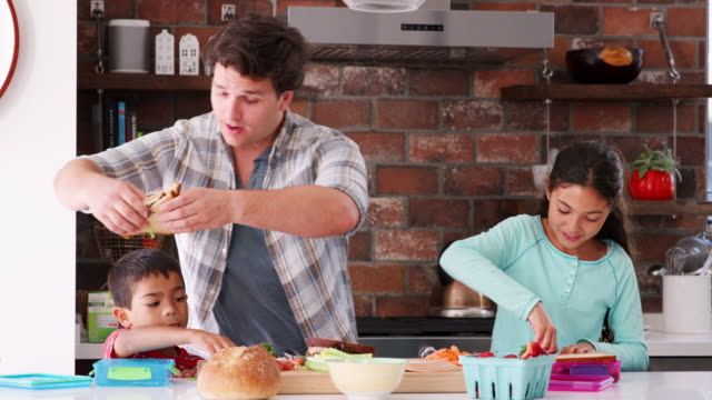 Padre-de-ayudar-a-los-niños-para-hacer-sándwiches-para-el-almuerzo-en-cocina