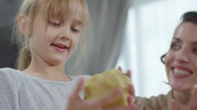 Cute-Girl-Helping-Mom-with-Kneading-Dough