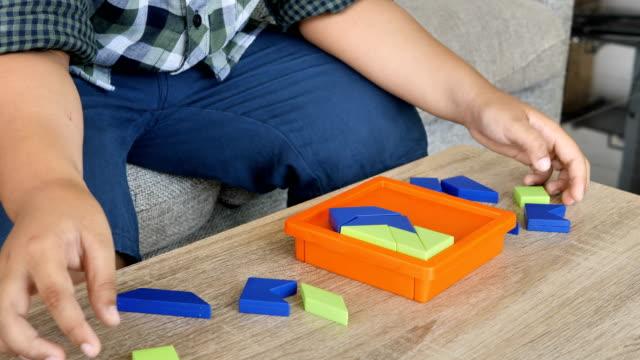 Chico-asiatico-para-resolver-rompecabezas-puzzle-en-escritorio-en-la-habitación-