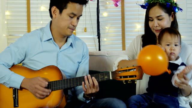 Vater-spielt-Gitarre-in-Mini-Party-zu-Hause-Menschen-mit-glücklichen-Familie-und-Party-Konzept-