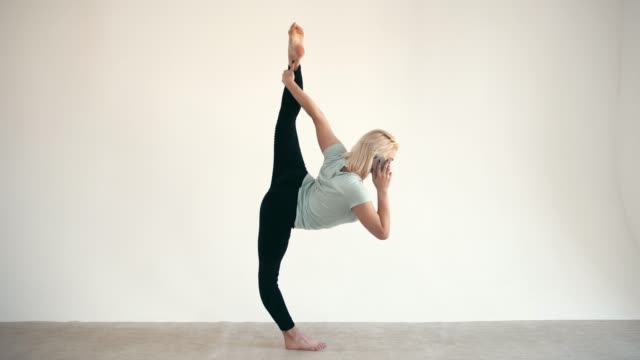 Model-size-plus-practice-yoga-lord-pose-and-use-smartphone-at-white-background
