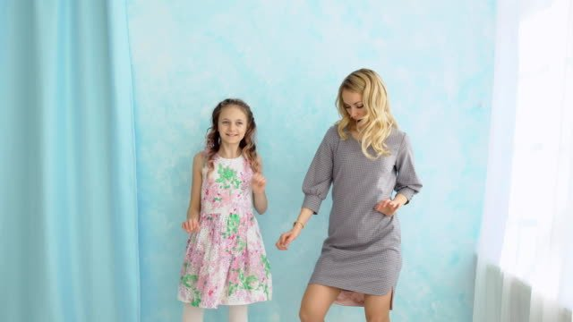 Mother-and-daughter-are-dancing-next-to-the-window-Fun-and-joy-