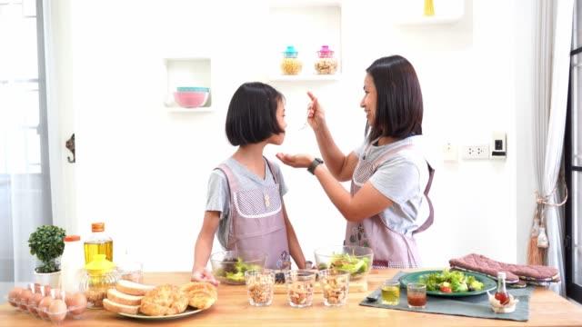 Madre-e-hija-cocinando-en-la-cocina-en-el-hogar-concepto-asiático-familia-feliz