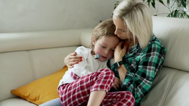 Medir-la-temperatura-de-su-hijo-enfermo-en-el-fondo-la-madre-Niño-enfermo-con-alta-fiebre-en-el-sofá-en-casa