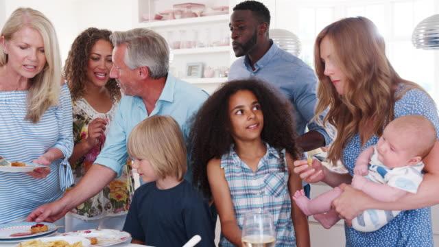 Grupo-de-familiares-y-amigos-para-fiesta-almuerzo-en-cocina---filmada-en-cámara-lenta
