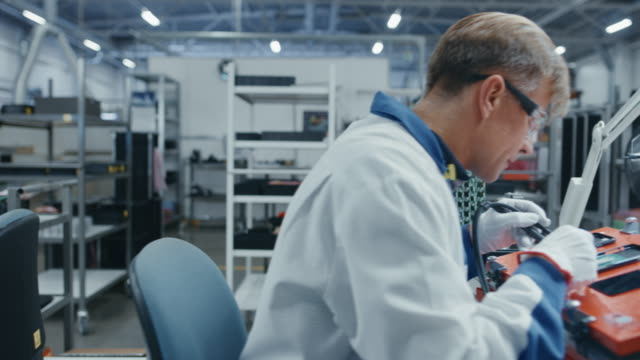 Time-Lapse-of-Young-and-Senior-Electronics-Factory-Workers-in-Blue-and-White-Work-Coats-Using-Pliers-and-Tweezers-to-Assemble-Printed-Circuit-Boards-for-Smartphones-High-Tech-Factory-Facility-