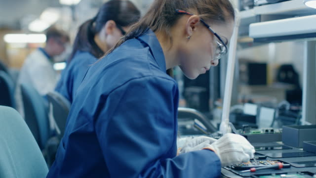 Female-Electronics-Factory-Workers-in-Blue-Work-Coat-and-Protective-Glasses-Assembling-Printed-Circuit-Boards-for-Smartphones-with-Tweezers-High-Tech-Factory-with-more-Employees-in-the-Background-