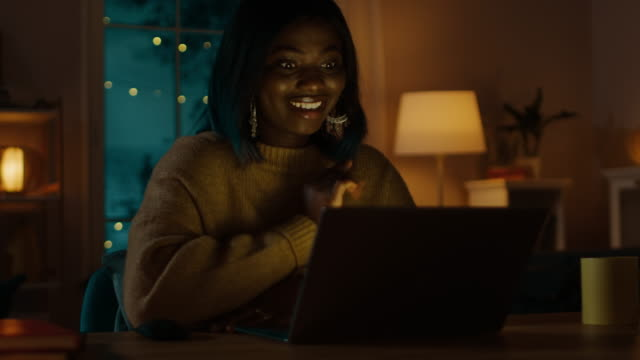 Portrait-of-Beautiful-Smiling-Black-Girl-Sitting-at-Her-Desk-Using-Laptop-to-Make-a-Video-Call-Says-Hello-In-the-Evening-Girl-Talks-with-Relatives-and-Friends-Using-Computer-Webcam-