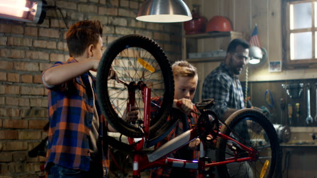 Father-and-his-two-sons-repairing-a-bike
