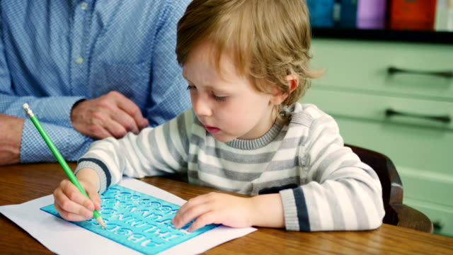 Father-Teaching-Son-How-To-Write-Using-Stencil