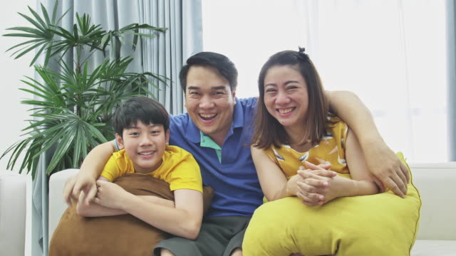 Slow-motion-of-asian-family-father-mother-and-son-on-couch-Looking-at-camera-with-smile-face-