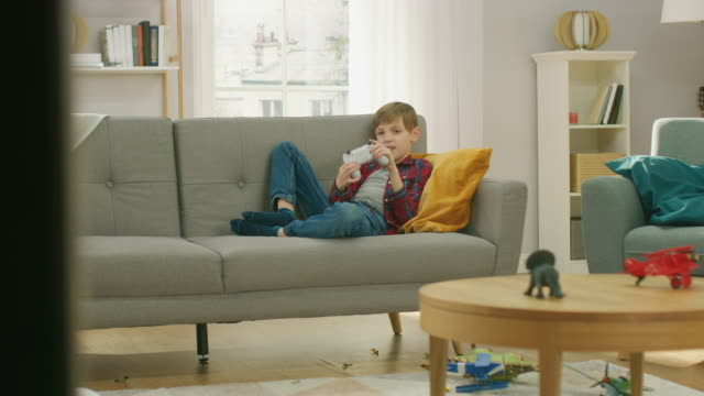 Adorable-Little-Boy-Laying-on-a-Couch-Playing-in-Video-Game-on-TV-Console-Using-Joystick-Controller-Boy-Playing-in-Videogame-at-Home-