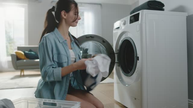 Bella-sonriente-mujer-morena-sienta-frente-a-una-lavadora-en-acogedoras-vaqueros-ropa-Ella-carga-la-lavadora-con-la-ropa-sucia-Amplia-y-luminosa-sala-de-estar-con-Interior-moderno-