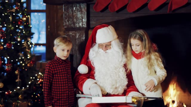 Santa-Claus-in-a-traditional-red-suit-sitting-in-the-middle-of-the-room-and-telling-stories-for-the-boy-and-girl-with-the-images-in-the-album-which-he-is-holding-in-his-hands-near-the-fireplace-on-a-cold-winter-evening-