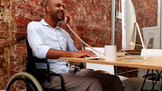 Casual-businessman-in-wheelchair-working-at-his-desk