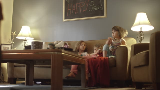 Little-girls-on-a-couch-watching-television-and-eating-donuts-and-one-girl-wipes-jelly-on-her-sister-s-nose