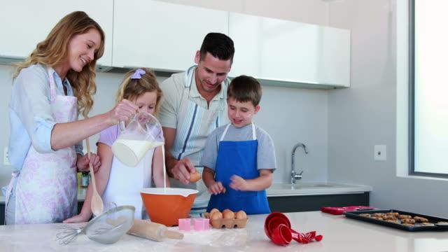Feliz-familia-joven-haciendo-juntos-tarta