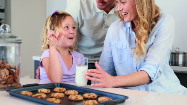 Niña-con-leche-y-galletas-con-sus-padres
