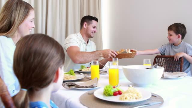 Familia-joven-feliz-en-la-mesa-de-comedor
